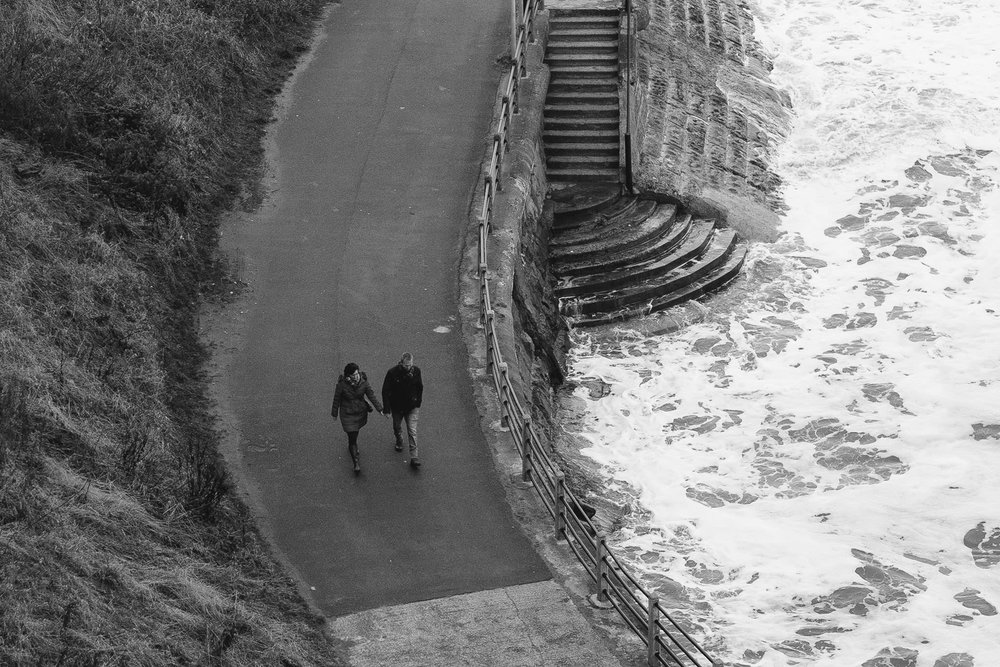 Black and white photo of couple walking hand in hand on promenade