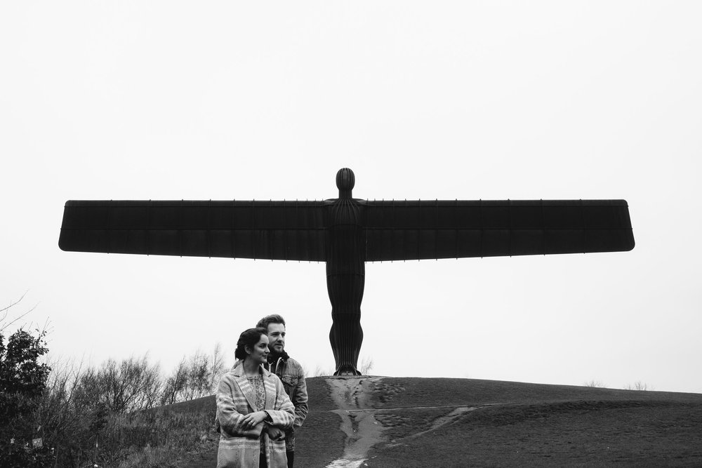 A black and white photo of a couple cuddling in front of the Angel of the North Newcastle
