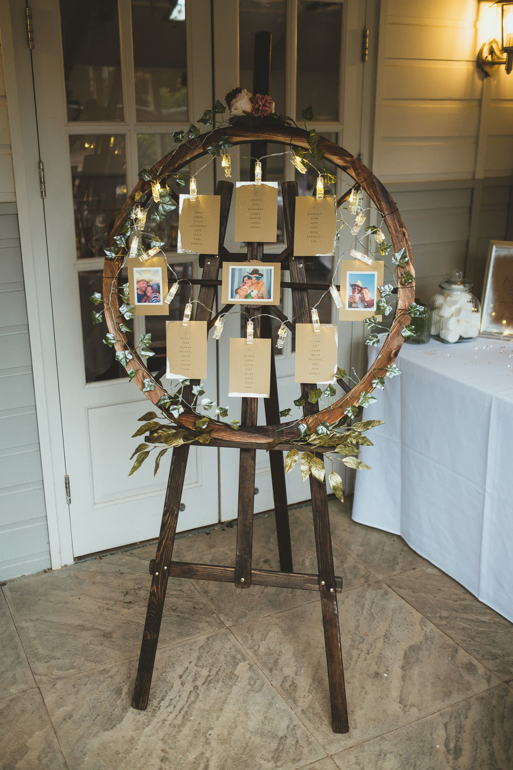 Wedding seating plan on wooden easel fringed by winter flowers