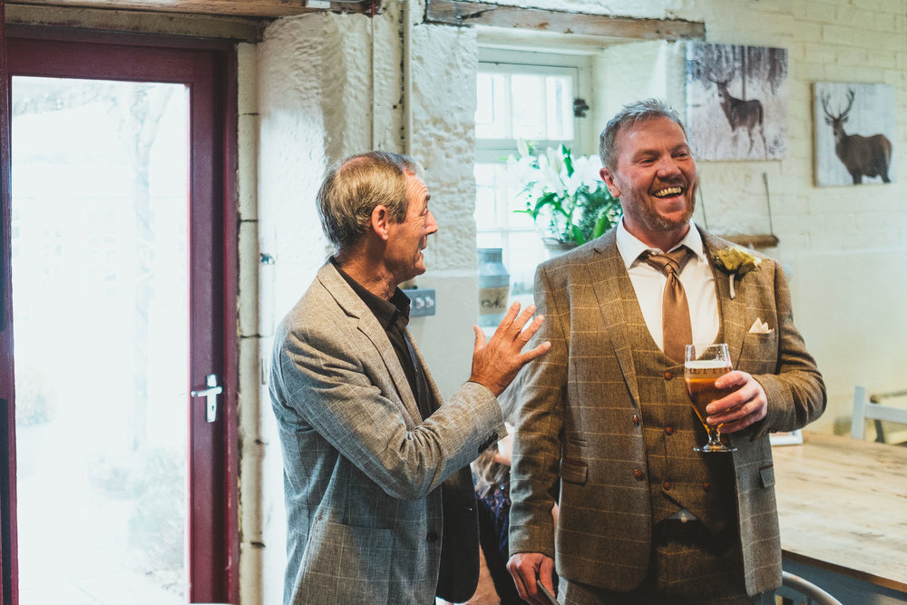 Groom laughing with friend before wedding ceremony in Newcastle
