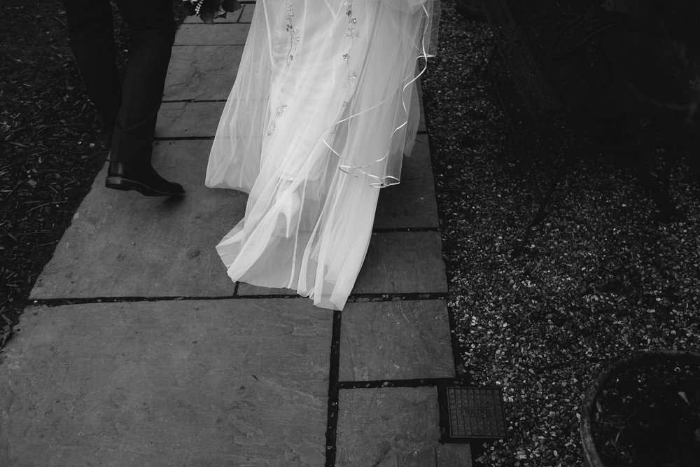 Black and white close up photo of the bride's dress as she arrives at the wedding venue