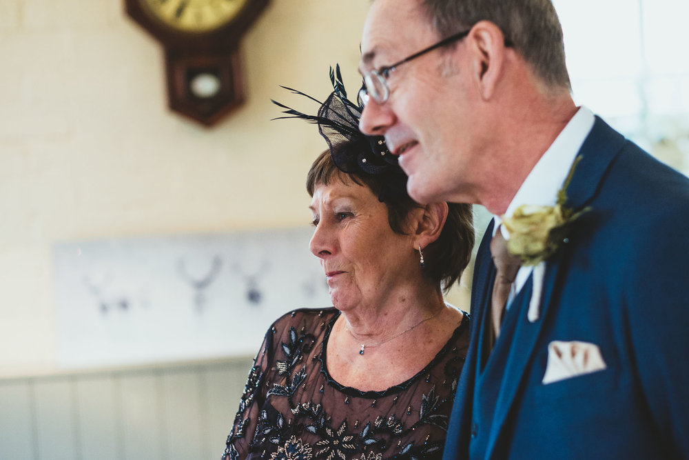 Bride's mother and father look on lovingly before wedding ceremony