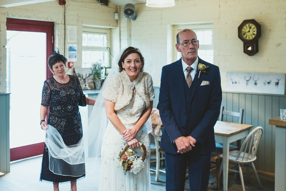 Bride smiles while her mother holds her wedding train