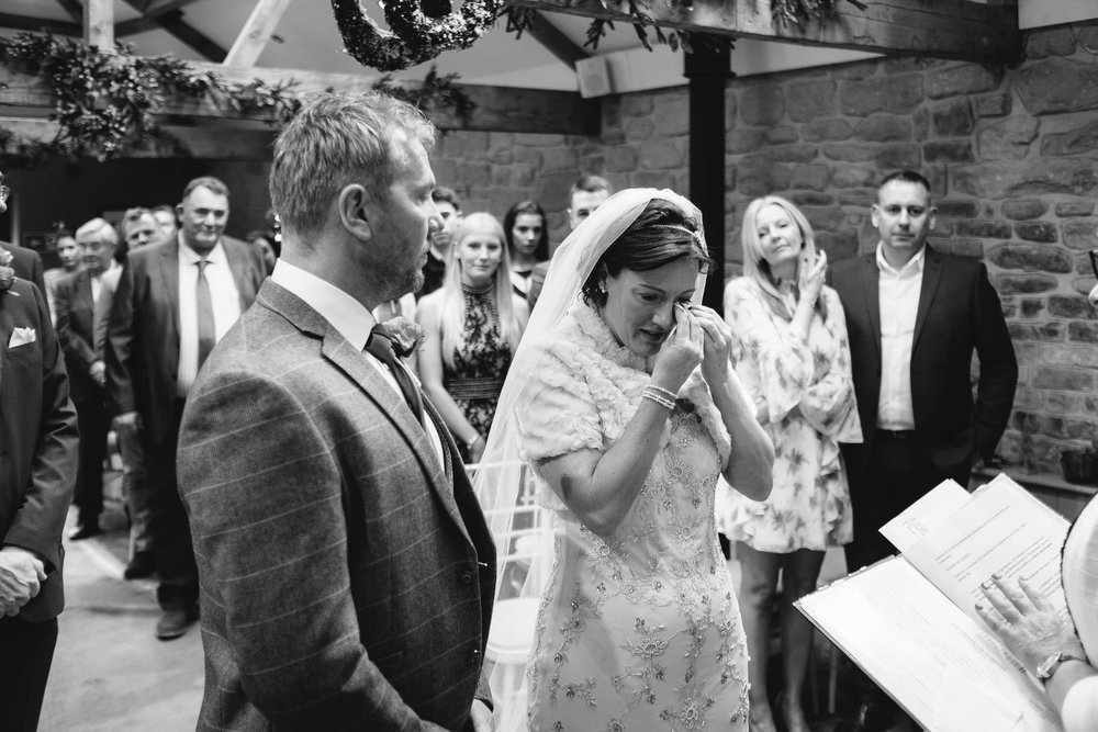 Black and white photo of the bride wiping away tears during her wedding ceremony