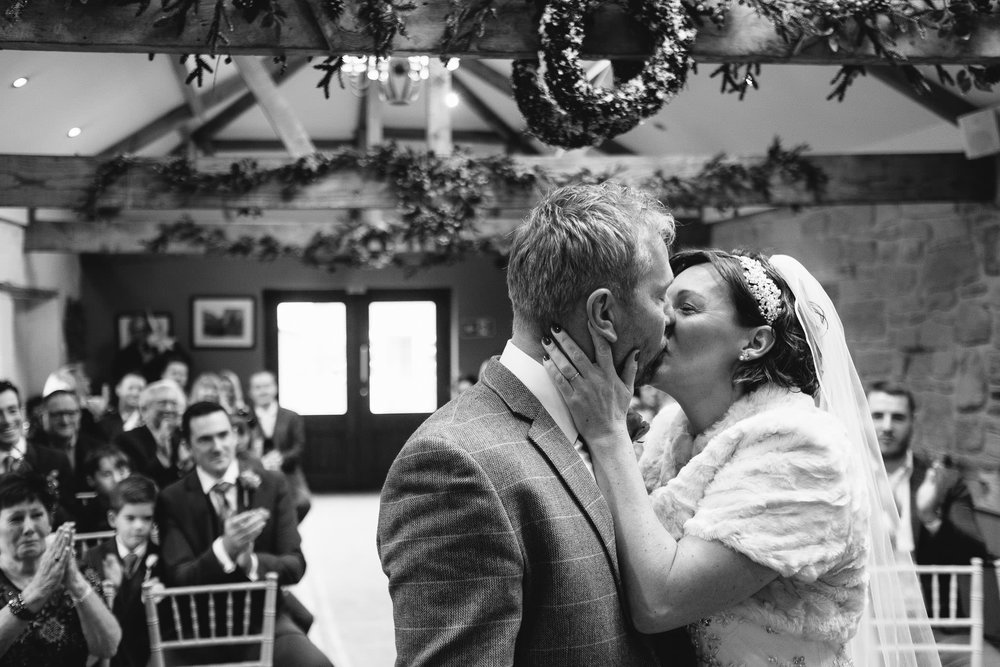 Black and white photo of the bride and groom kissing during wedding ceremony