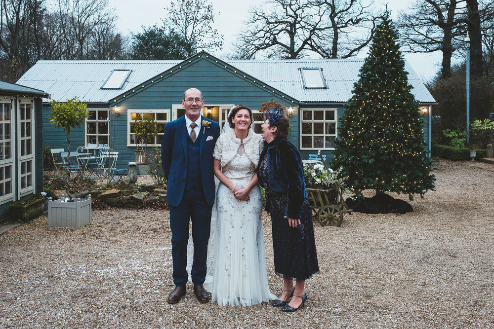 Bride poses with her father and mother who is screaming