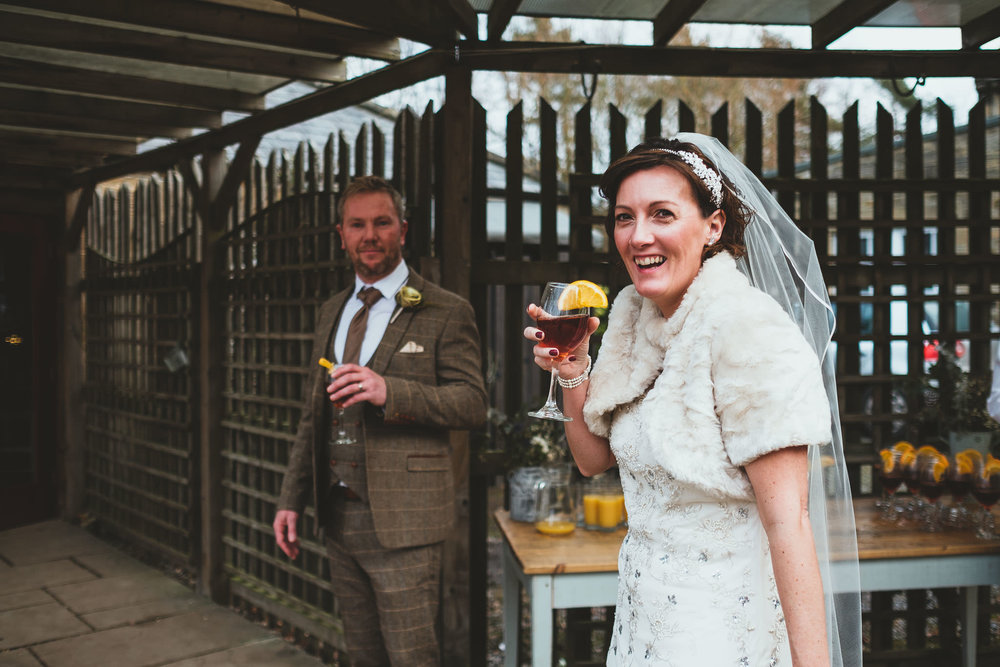 Bride smiles at camera while holding cocktail