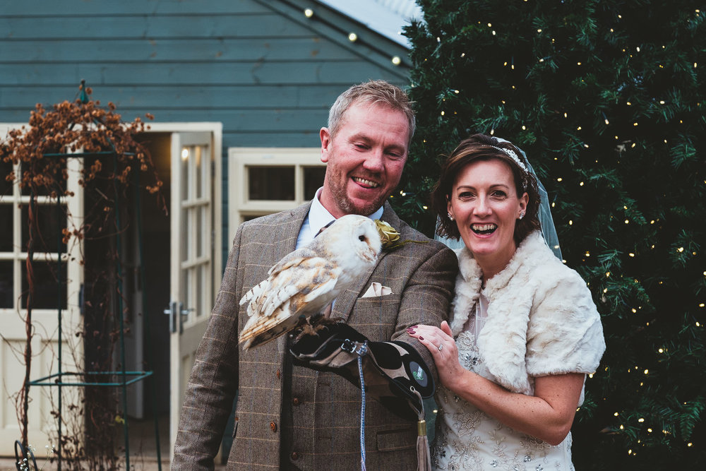 Bride and groom laugh while holding owl