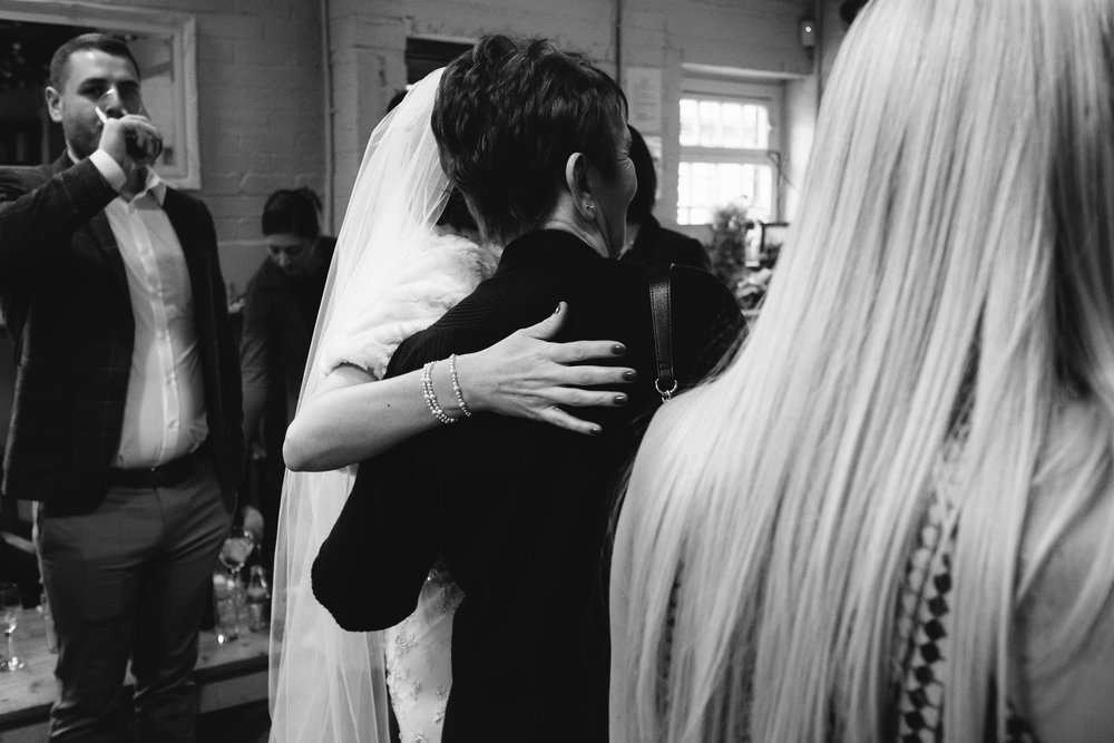 Black and white photo of the bride cuddling guest