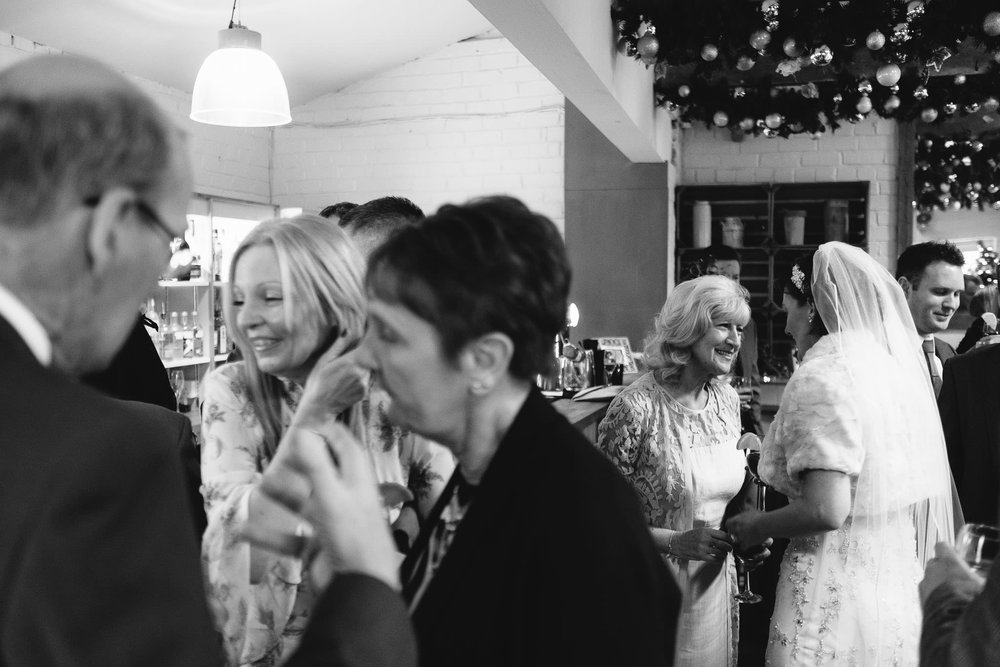 Black and white photo of bride speaking to guests during wedding reception at The Parlour at Blagdon