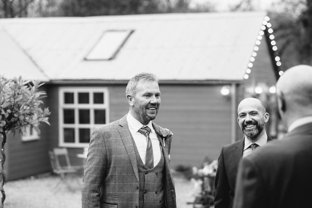 Black and white photo of groom laughing with guests in courtyard at The Parlour at Blagdon