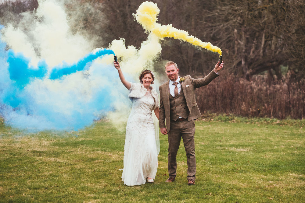 Bride and groom hold hands while letting off smoke bombs at The Parlour at Blagdon
