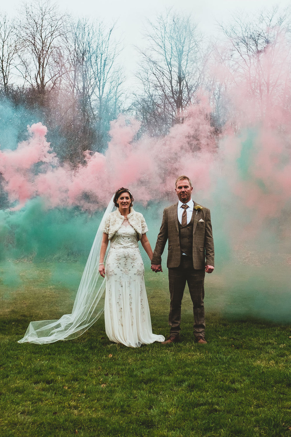 Portrait photo of the bride and groom holding hands while coloured smoke drifts behind