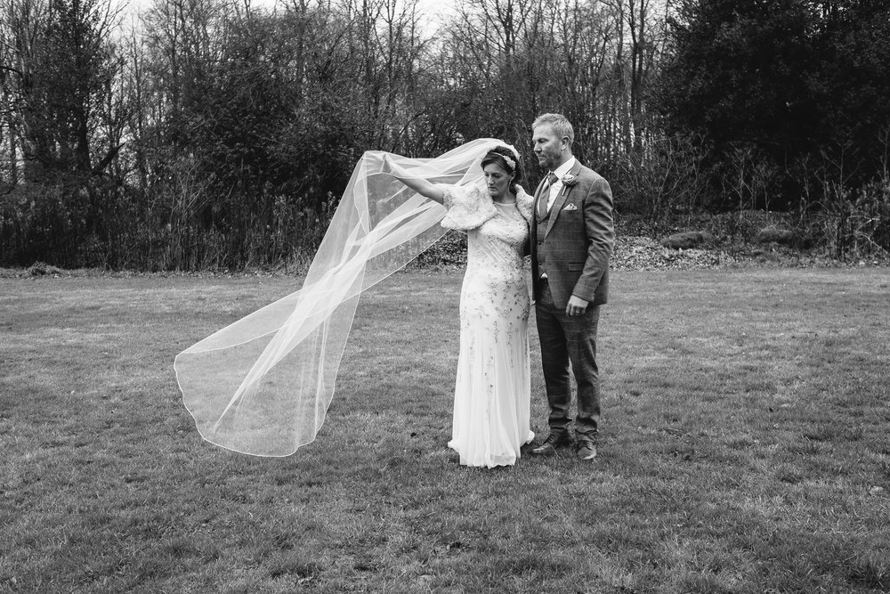 Black and white photo of the bride and groom with the bride's veil blowing in the wind
