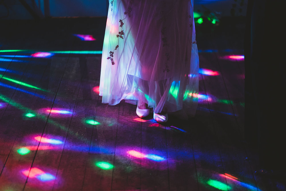 Close up of the brides dress lit by disco lights