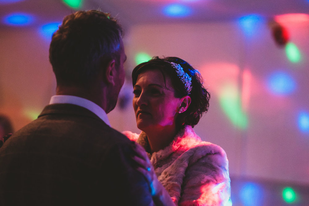 Bride and groom first dance lit by disco lights