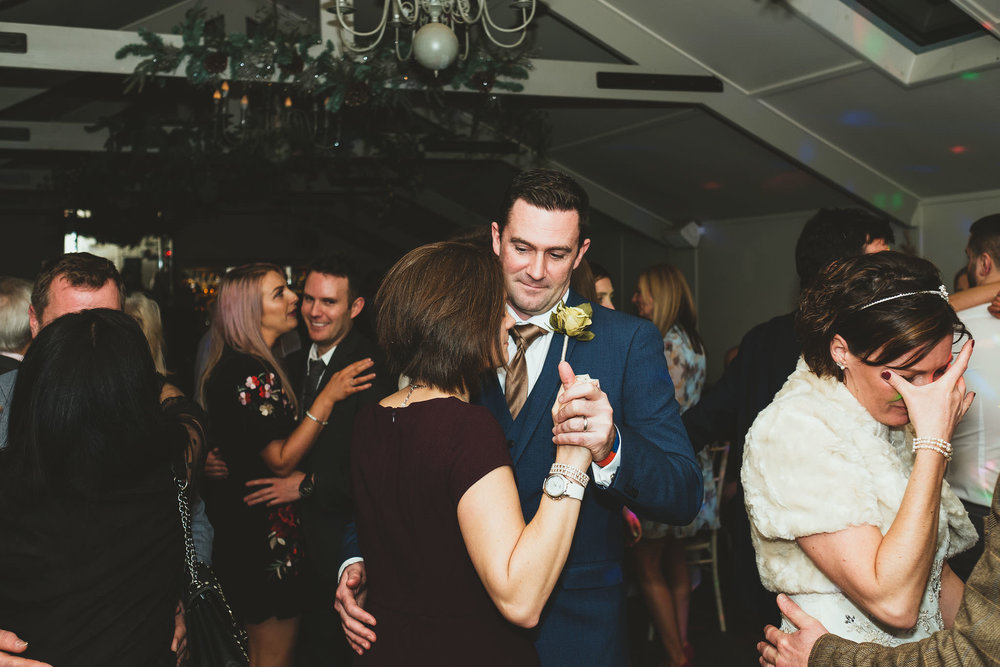 Couples dance on wedding dance floor while bride cries