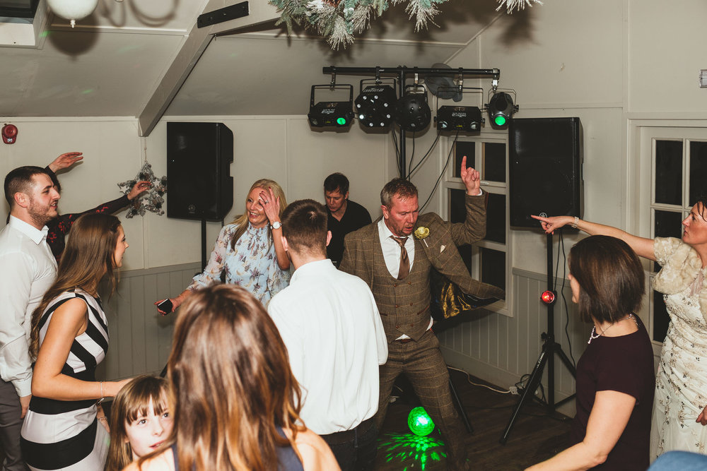 Bride and groom point at each other on wedding dance floor