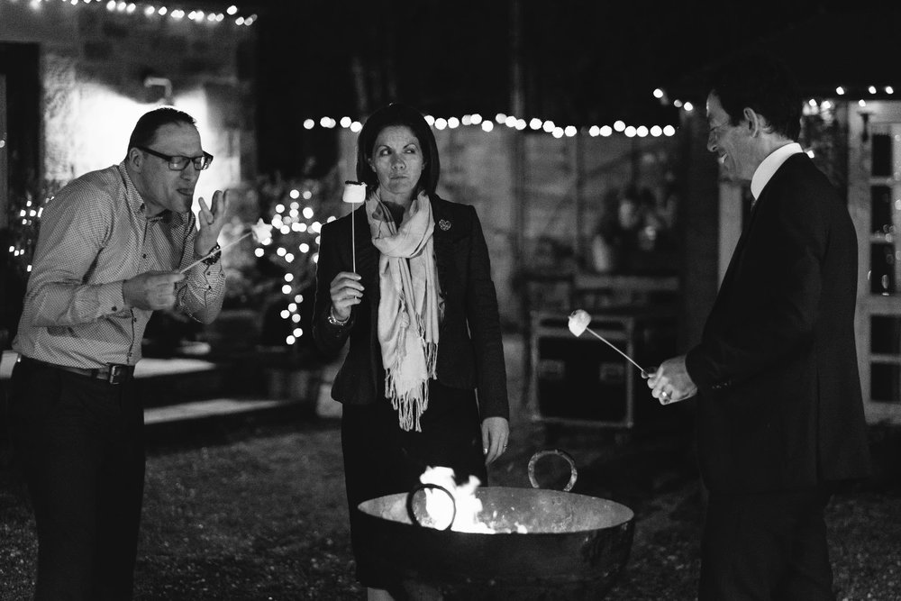 Black and white photo of wedding guests eating marshmallows near fire pit