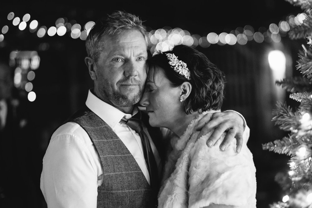 Black and white close up photo of bride and groom hugging with fairy lights behind