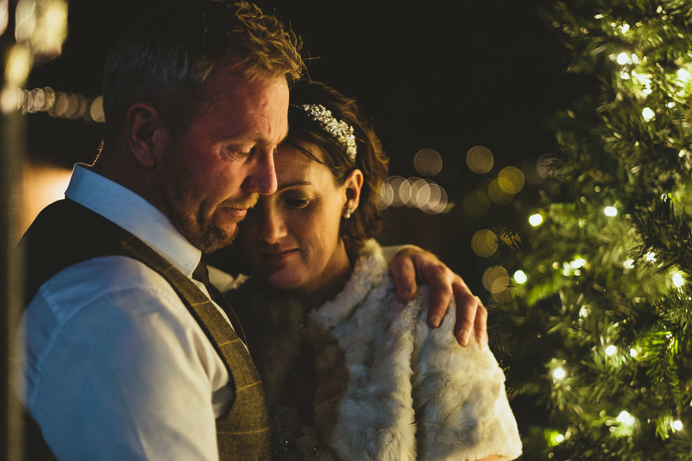 Close up of bride and groom hugging outside lit by Christmas tree