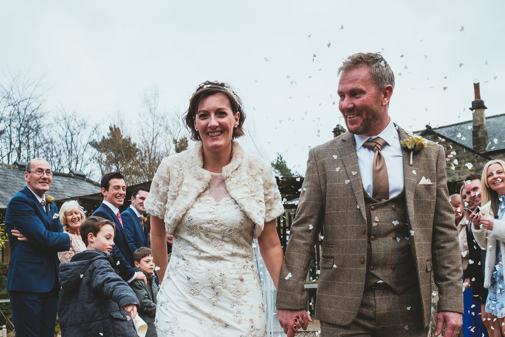 Angela and Dave being showered with confetti following their wedding ceremony.