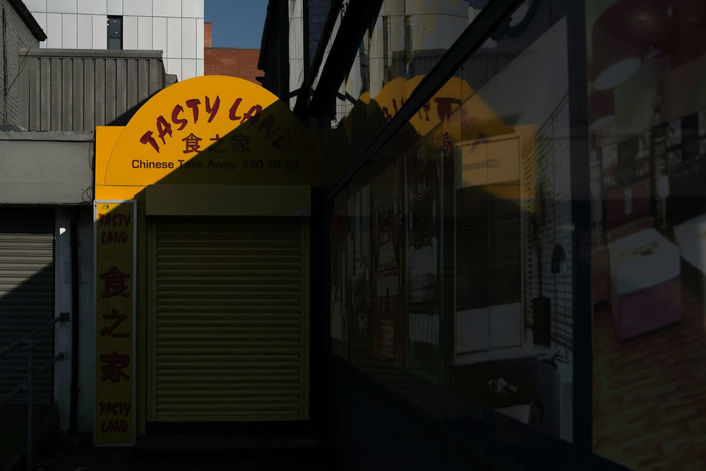 A colourful Chinese takeaway sign is split by harsh shadow