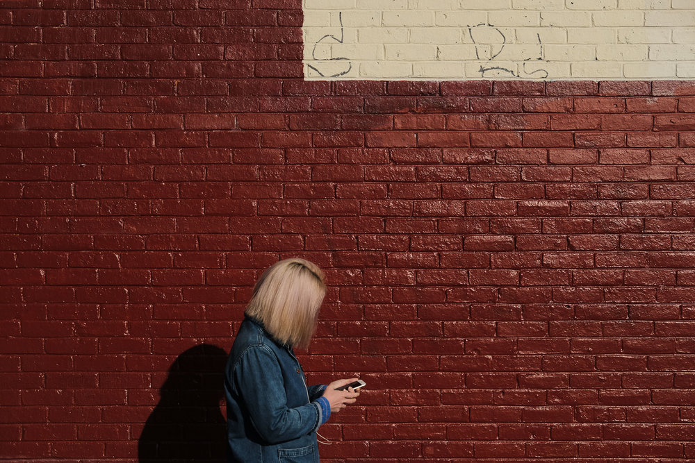 A woman walks past a red wall while looking at her phone