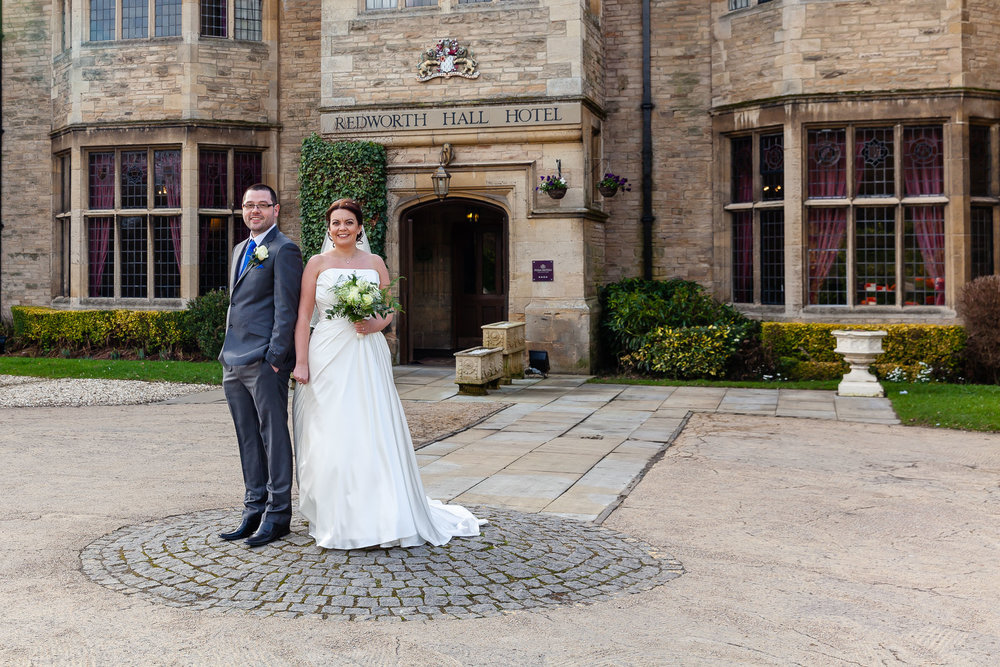 Lynne & James at the entrance to Redworth Hall wedding venue in Durham