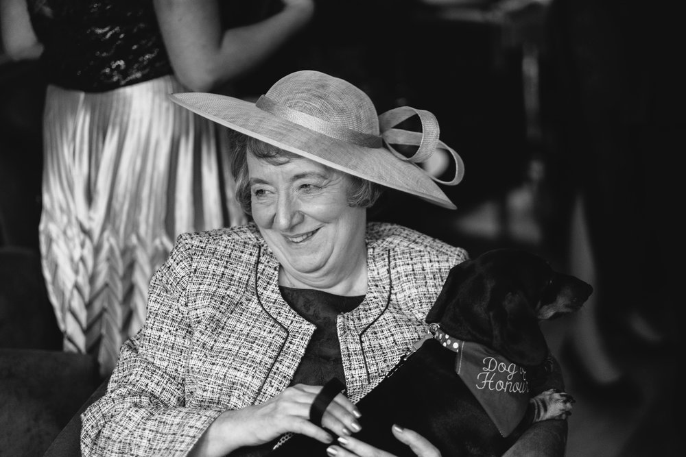 A black and white photo of the mother of the groom sitting with a sausage dog in her lap