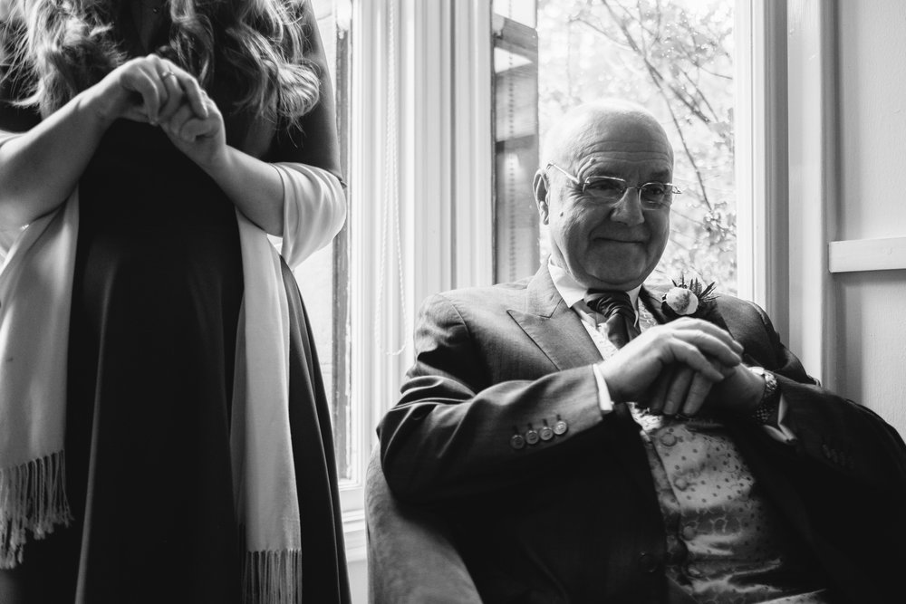 A black and white photo of the father of the groom sitting thoughtfully