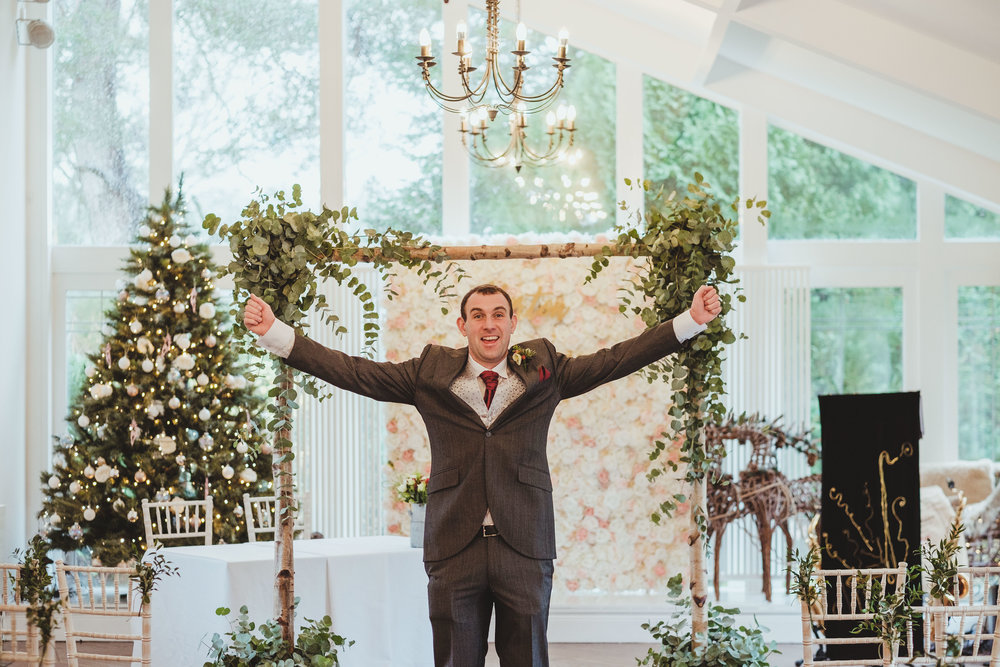 Groom cheering for the camera before the wedding ceremony