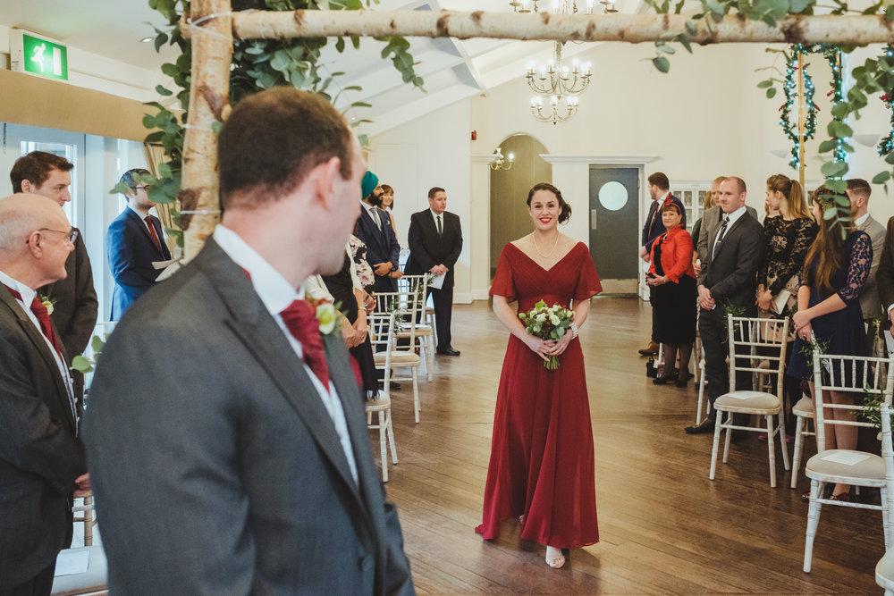 Groom watches bridesmaid wearing red dress walking down aisle