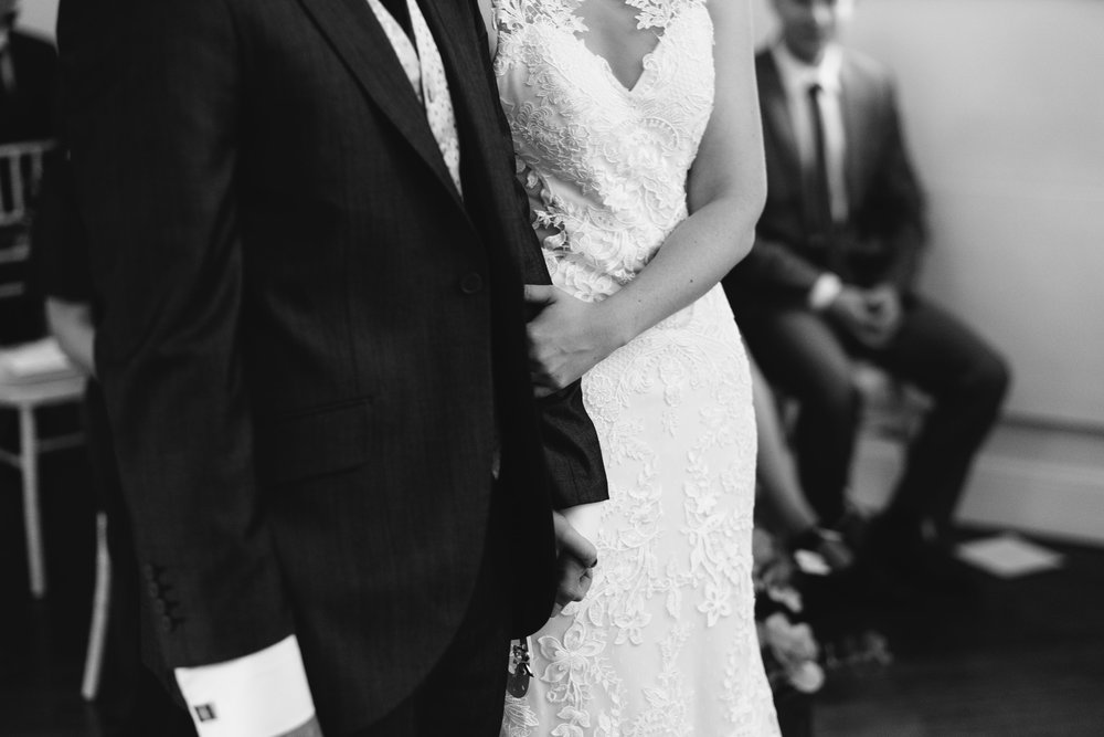 A black and white photo of the bride and groom arm in arm during wedding ceremony