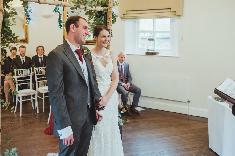 Bride and groom hold hands during the wedding ceremony at Horton Grange