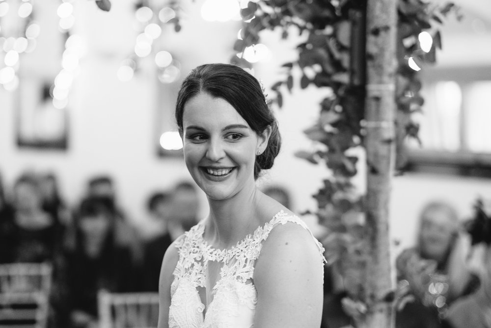 A black and white photo of the bride smiling during the wedding ceremony