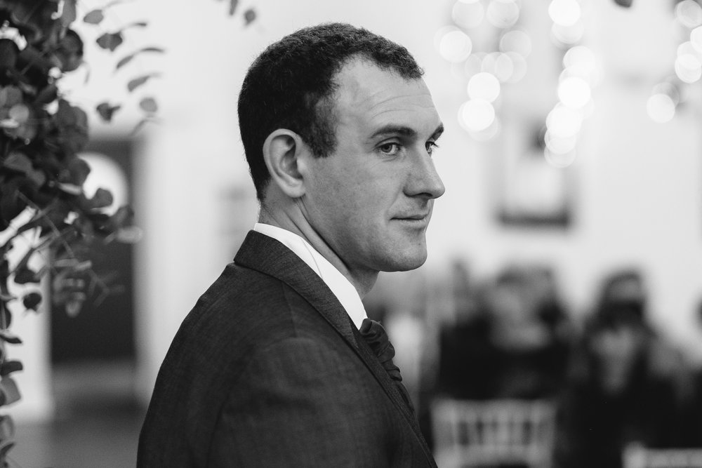 A black and white photo of the groom smiling during the wedding ceremony