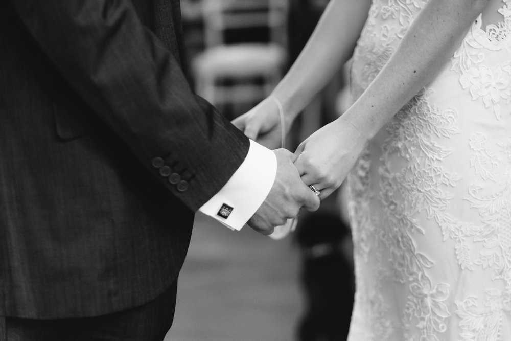 A black and white photo of the bride and groom holding hands during the ceremony