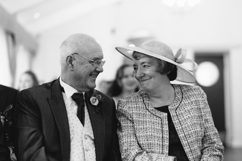 A black and white photo of the groom's parents lovingly looking at each other during the wedding