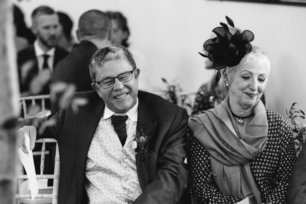 A black and white photo of the bride's parents laughing after the wedding