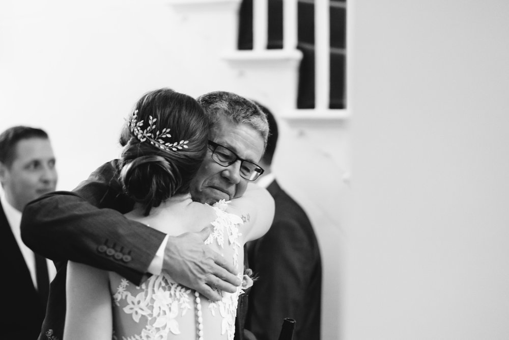A black and white photo of the bride's father hugging the bride