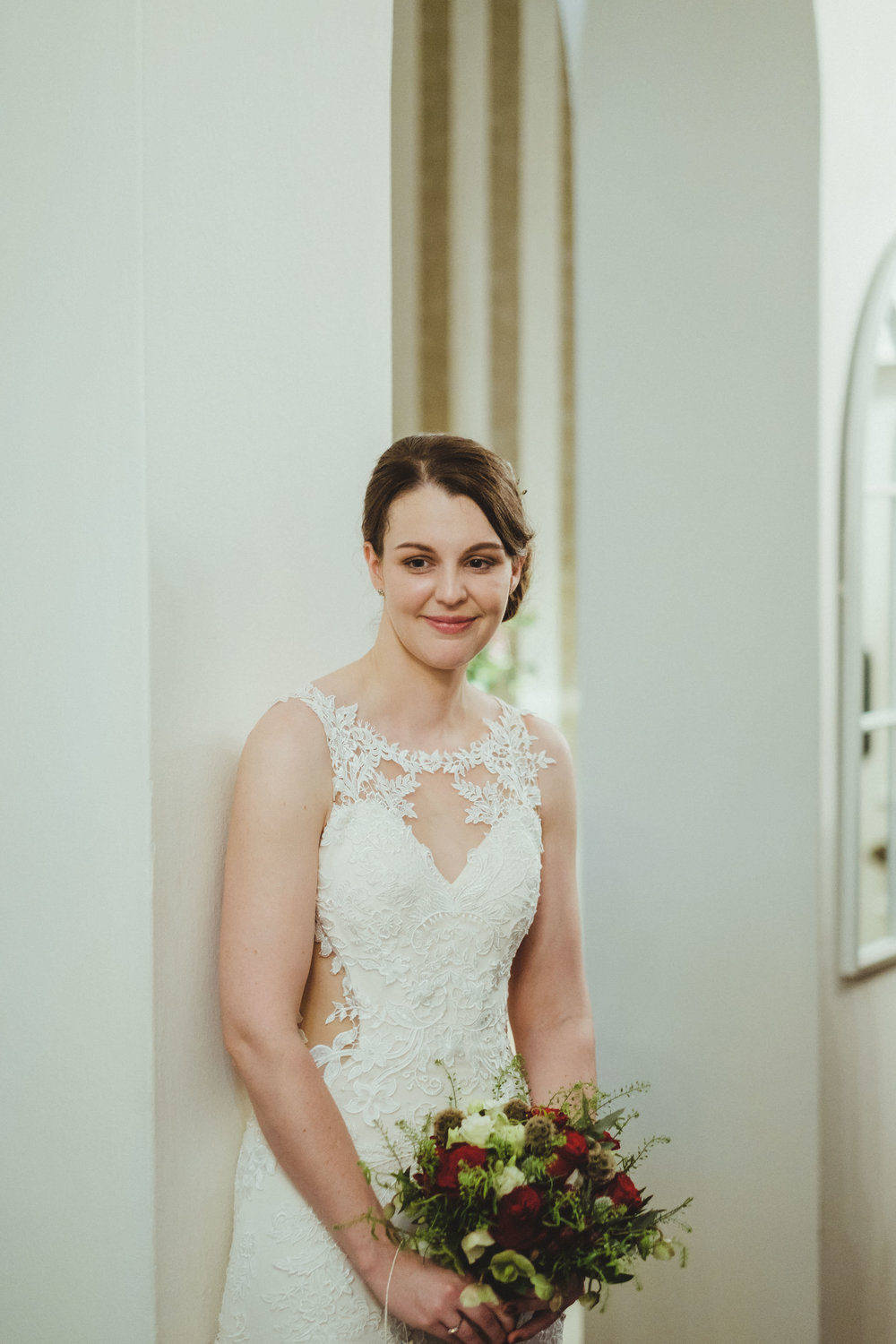 Bride leaning against a pillar and smiling at Horton Grange