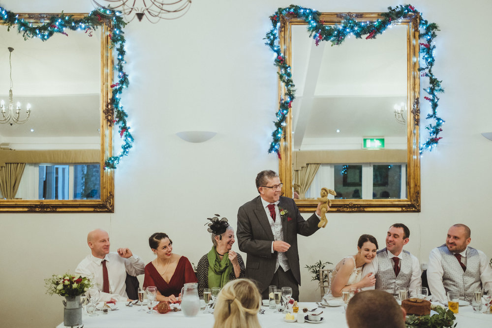 Father of the bride holding up a teddy bear during wedding speech