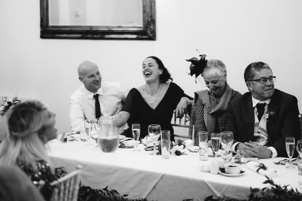 A black and white photo of the guests laughing at a wedding speech in Northumberland