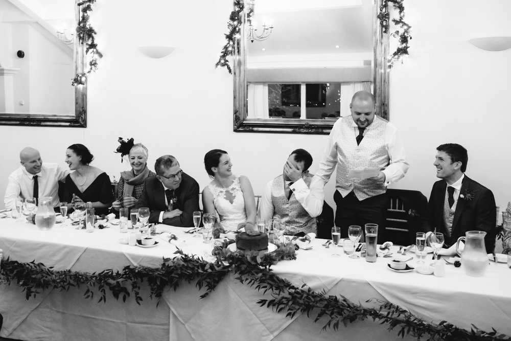 A black and white photo of groom with his head in his hands during a wedding speech