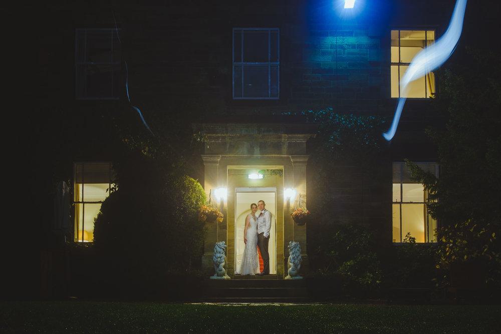 Couple pose at night in doorway of Horton Grange in Northumberland