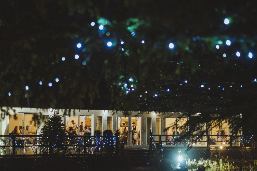 Fairy lights twinkle in the darkness at a winter wedding at Horton Grange