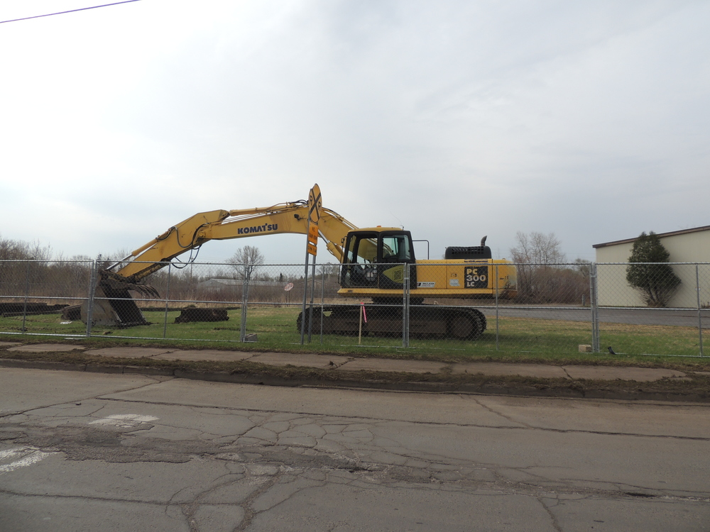 Above: An excavator waits to demolish structures on site in order to make way for a new Kwik Trip at the corner of Grand Avenue and Raleigh Street in West Duluth.