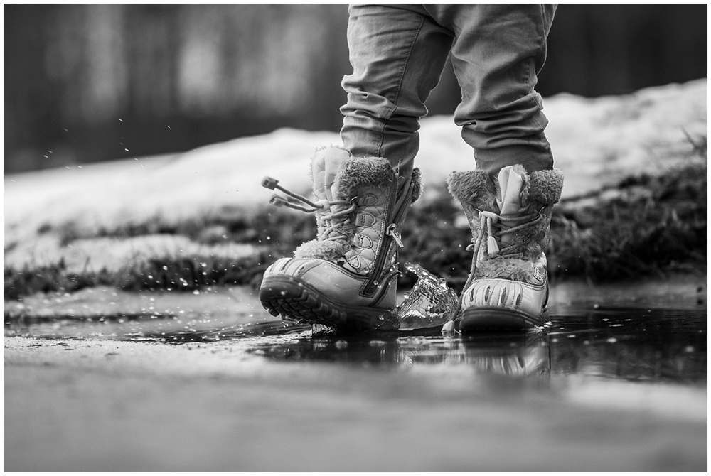 toddler winter boots splashing in puddle in black and white