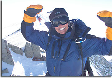 Mountain climber Lori Schneider raises her arms in victory as she reaches the Mt. Vinson Massif summit in Antarctica.